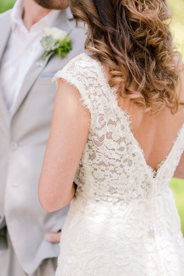 back detail of brides lace gown by Calla Blanche and her hair by Kara Russell