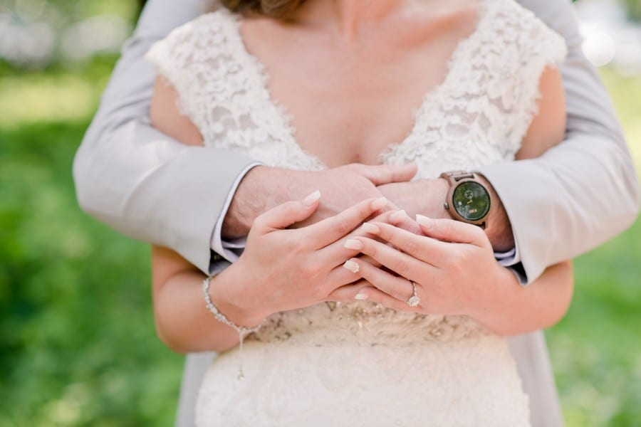 Close up of the bride and grooms hands and he has his arms wrapped around her chest, with her hands on top of his. Highlighting his watch by Jord Watches and her custom ring by Pave Goldsmiths