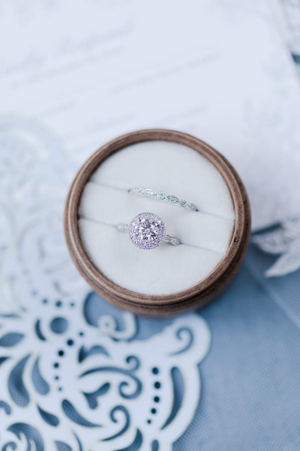 Wedding details: the brides custom round diamond engagement ring with diamond halo in a ring box with her antique style wedding band displayed on top of the wedding invitation