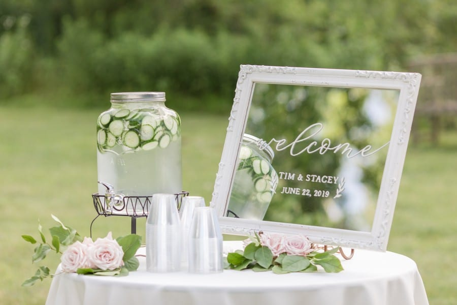 Wedding details: outside of the ceremony location, a welcome sign, with the bride and grooms name on it, along with the date of the wedding, along with cucumber water service.