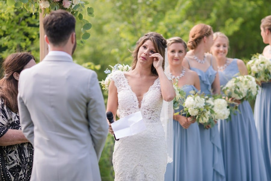 The bride wiping away a tear as she says her vows to her groom. The bride is wearing a sleeveless, lace vneck Calla Blanche wedding gown