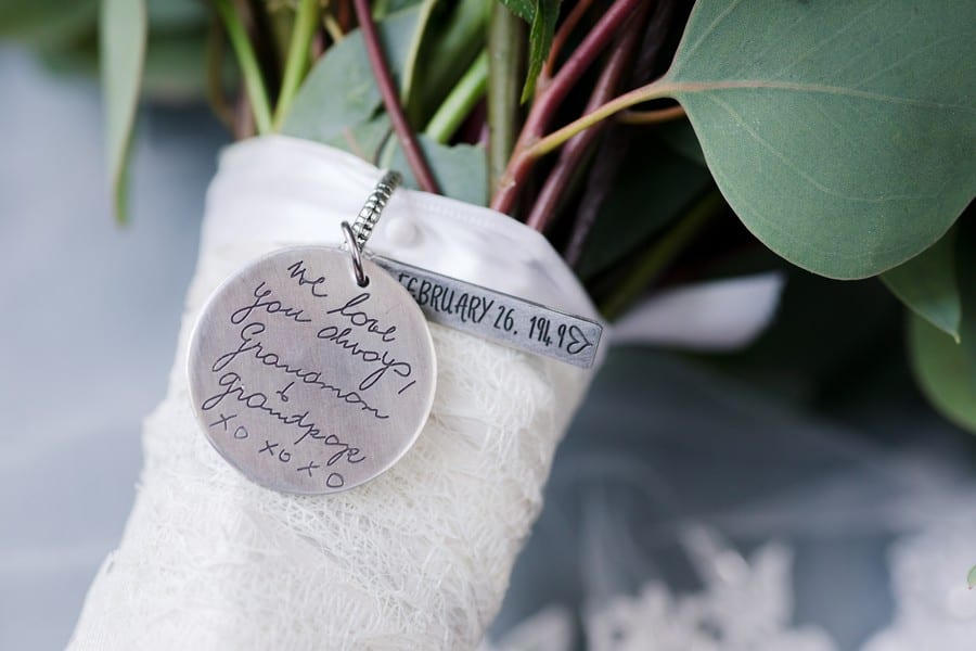 A close up of a personalized charm attached to the bridal bouquet from the brides grandparents