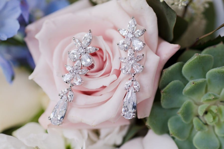 close up of the brides floral and teardrop crystal earrings on a light pink rose in the bridal bouquet