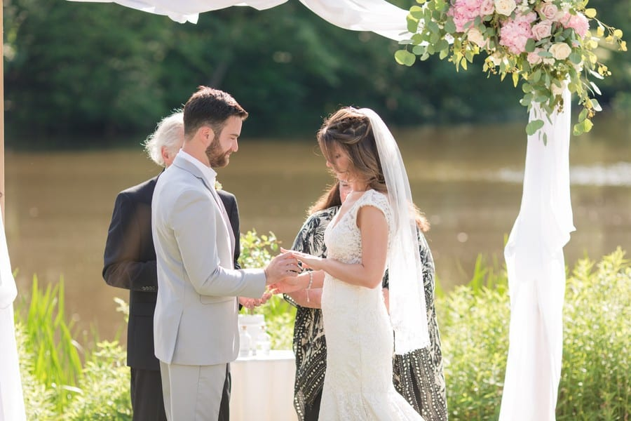 The bride and groom exchange rings under a white fabric wrapped wooden altar piece, decorated with pink florals with greenery at the top left corner in front of the lake at the Mountain Lakes House in Princeton, NJ