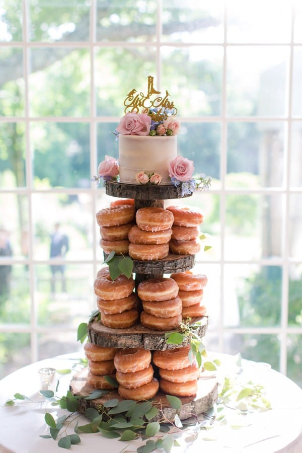 4 tier donut cake wedding cake, on custom wood slice tower. The top of the cake is an actual cake in an off white with dusty rose, purple and light pink florals and a gold personalized cake topper. Food from the Gingered Peach, the cake stand made by the Father of the Bride and the Groom. Placed in front of a well lit window at the Mountain Lakes House in Princeton