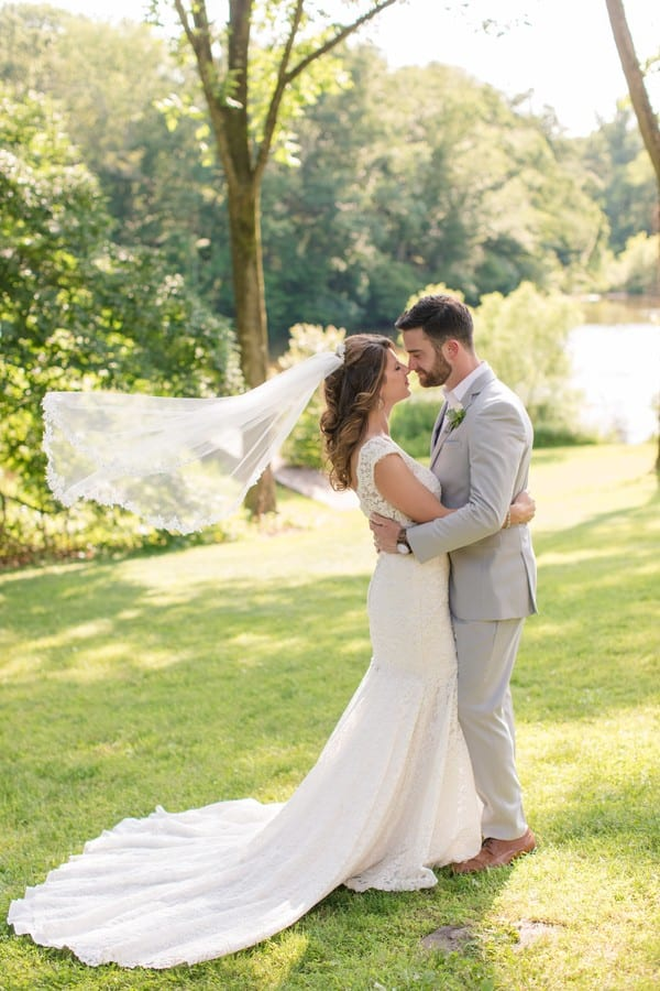 the bride in her grooms arms, veil blowing in the wind behind her, their noses touching, eyes closes, the grounds of the Mountain Lakes House behind them.