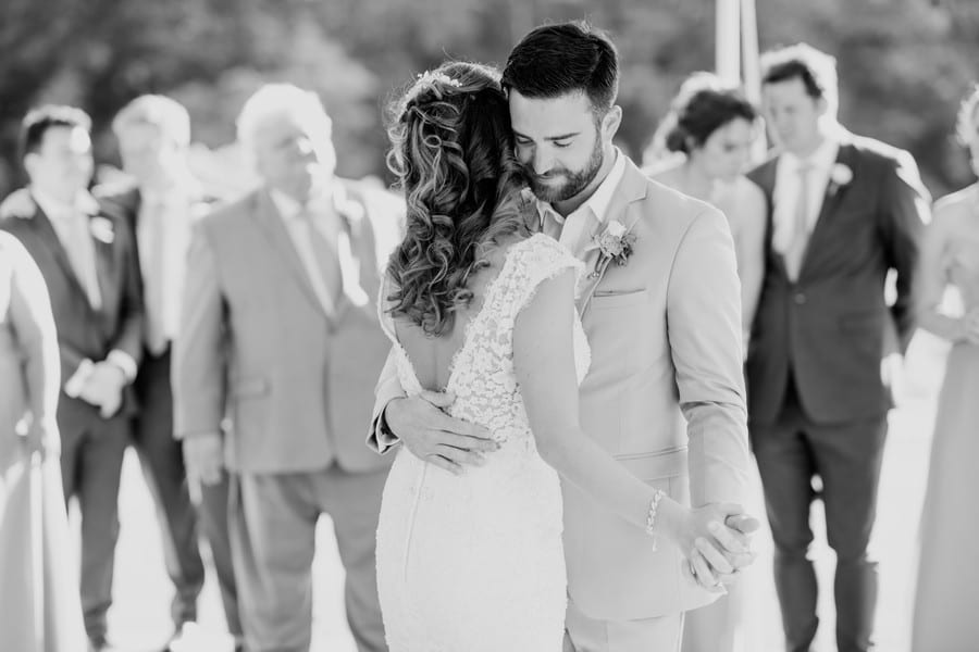 Black and white photo from behind the bride whom is dressed in a mermaid style lace v-neck gown by Calla Blanche with her groom in a grey suit during their first dance
