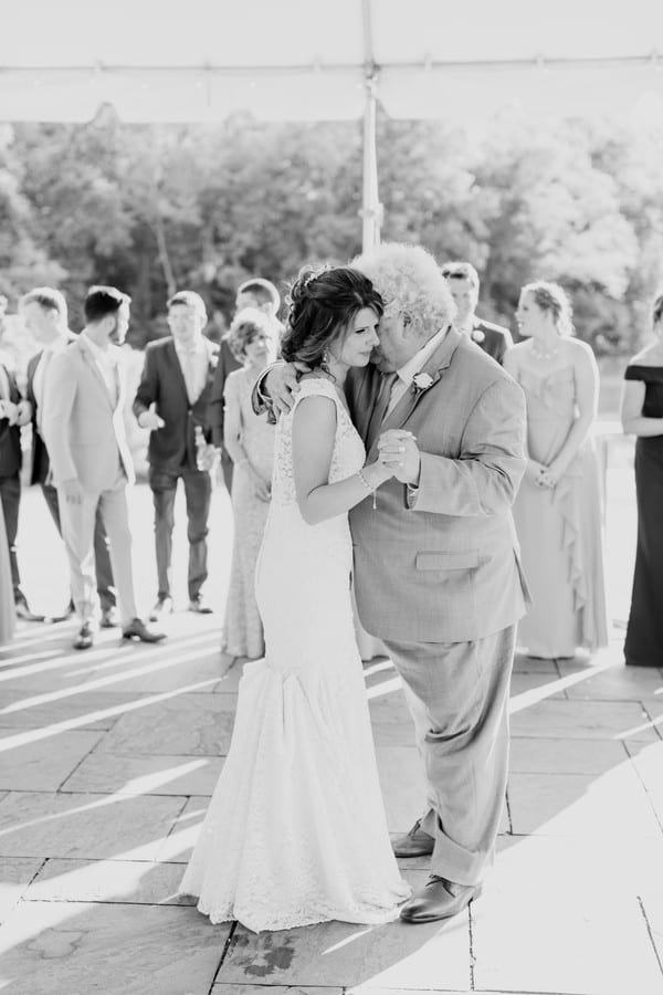 black and white full length photo of the bride dancing with her father.