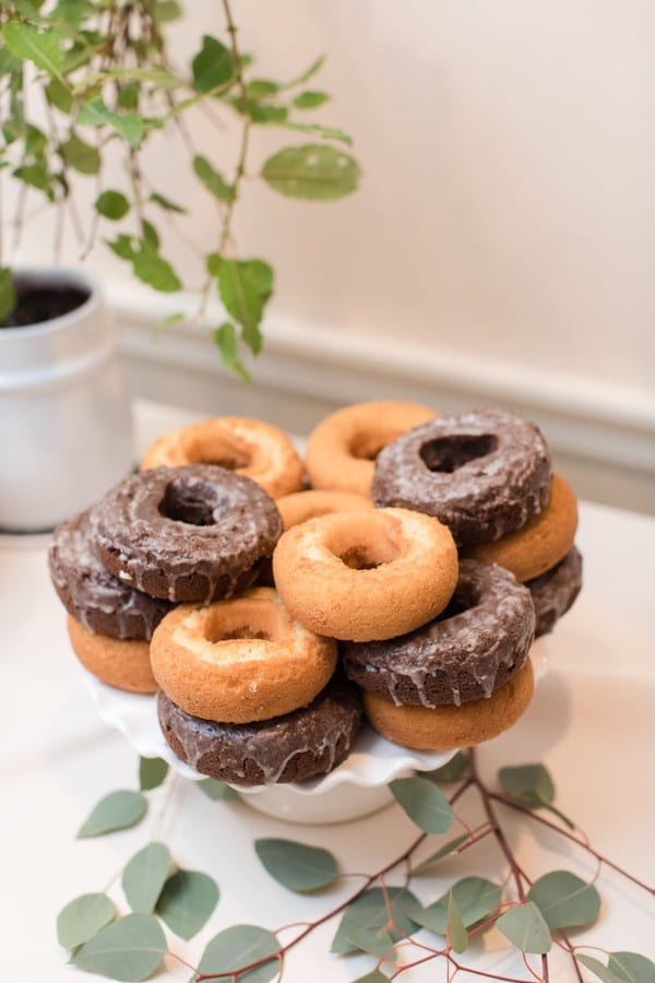 An assortment of chocolate glazed donuts and plain cake donuts on display on a white ruffled edge cake plate. Sparse greens are on on the table underneath the display of donuts