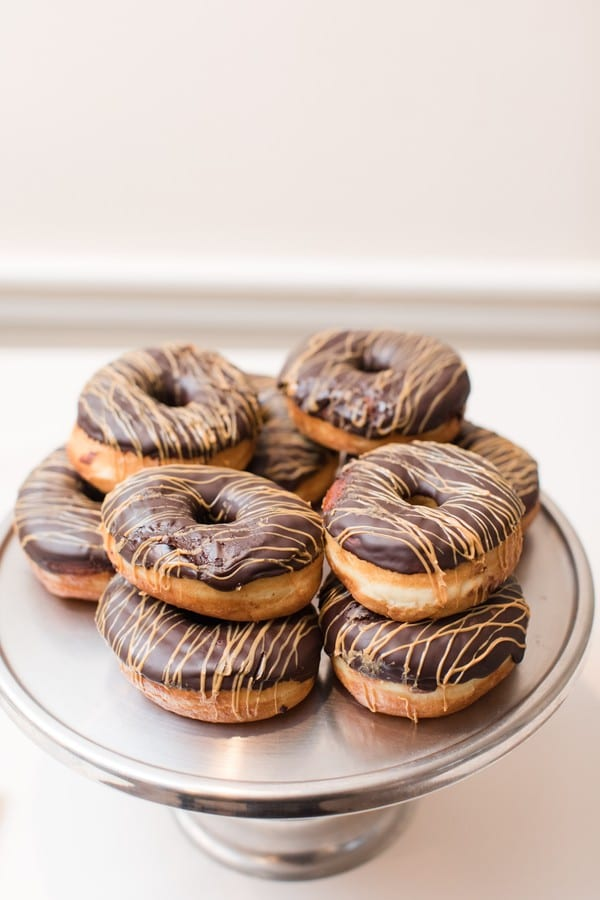 Donuts displayed on a brushed silver cake plate during dessert