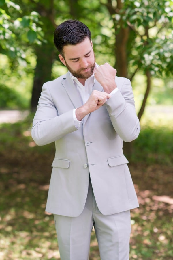 portrait of groom adjusting his cufflinks of his light grey suit without tie