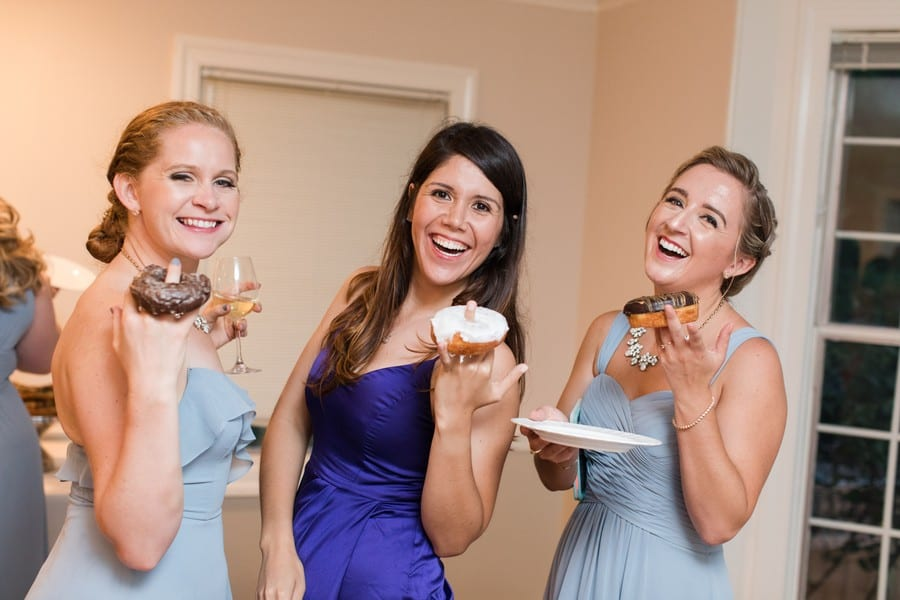 Members of the bridal party in light blue gowns of varying styles by Azazie show off the various donuts they are eating as part of the dessert