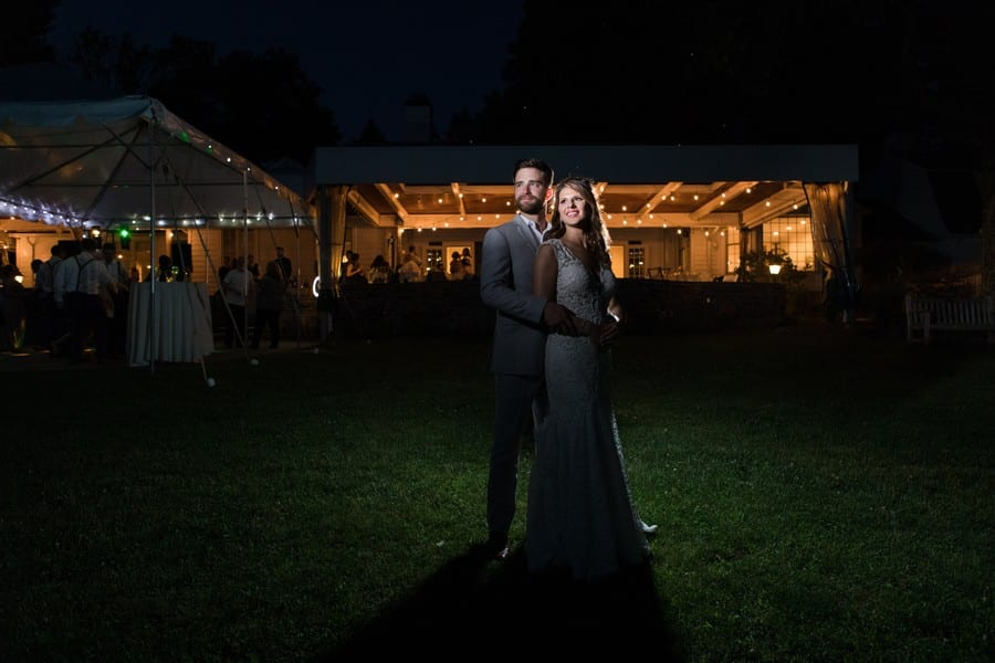 """Bride standing in front of her groom in a """"prom style pose"""", both smiling and gazing past the photographer off into the distance. Both the tented area and wooden bar area at the Mountain Lakes House have lights strung around their ceilings"""