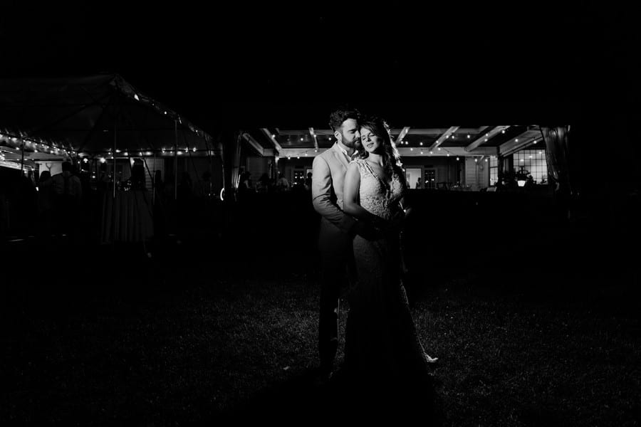 Black and white photo of the bride in her grooms arms, standing outside in front of a lit up outdoor bar area. The shot is done so everything else is very dark except for the lights that are strung around the ceiling of the bar area, and the torso's of the bride and groom