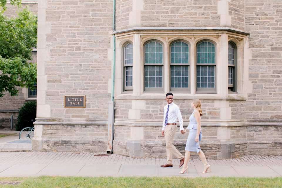 Engaged couple walk in front of Little Hall on the campus of Princeton University. She is wearing a pale blue peplum dress by John Paul Ataker from Castle Couture. He is wearing a shirt by Calvin Klein, pants by Old Navy, tie from Bar III. Jaye Kogut Photography, New Jersey engagement photographer