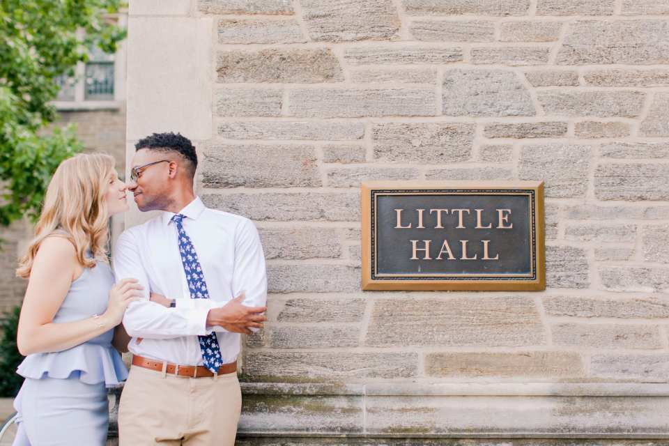 couple standing against the brick wall outside Little Hall on the campus of Princeton University. His arms are crossed, looking to his right at her, nose against hers as she has her arms on his upper right arm.