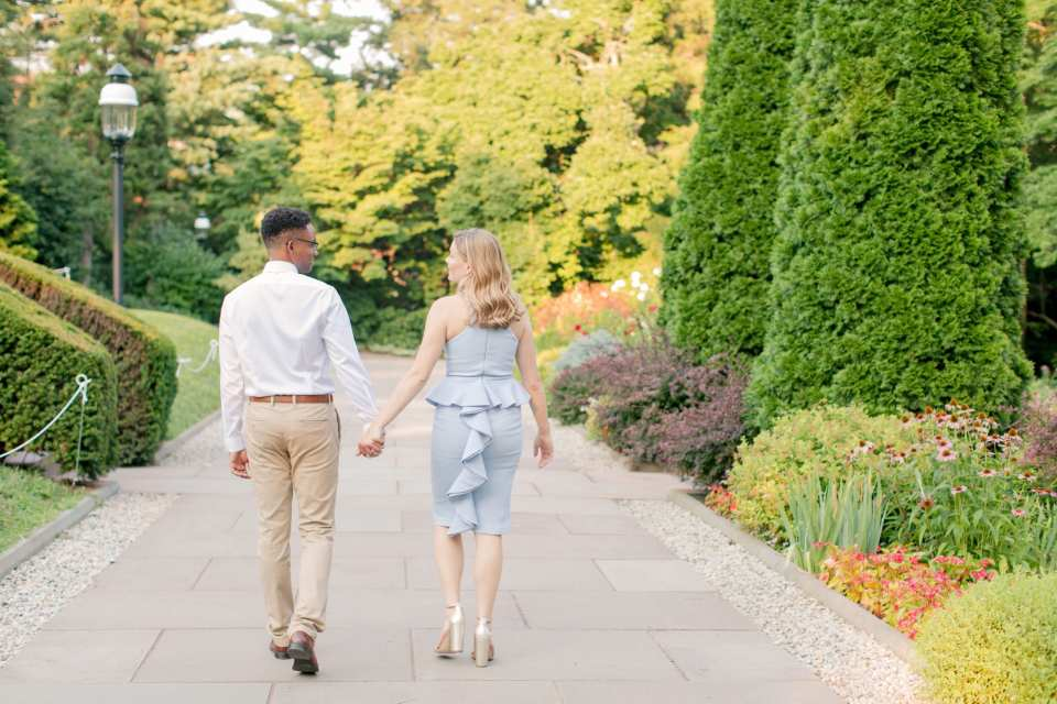 Couple facing away from camera, holding hands. Blue sleeveless peplum dress with back ruffle by John Paul Ataker from Castle Couture, gold block heels by Sam Edelman. His shirt by Calvin Klein, pants by Old Navy. Photo by Jaye Kogut Photography, NJ engagement photographer