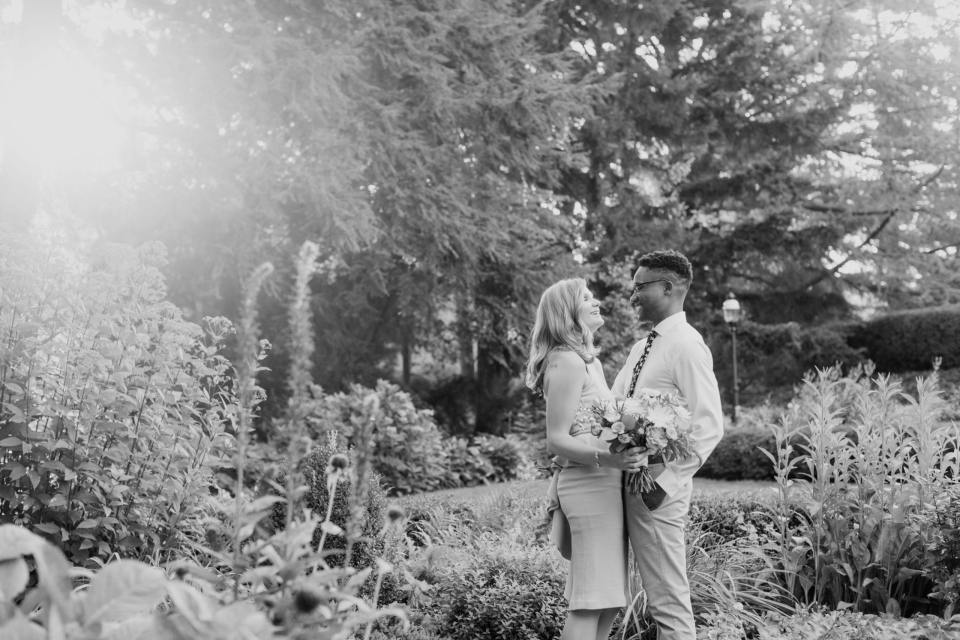 black and white photo of the couple standing in a garden, looking at one another, laughing.