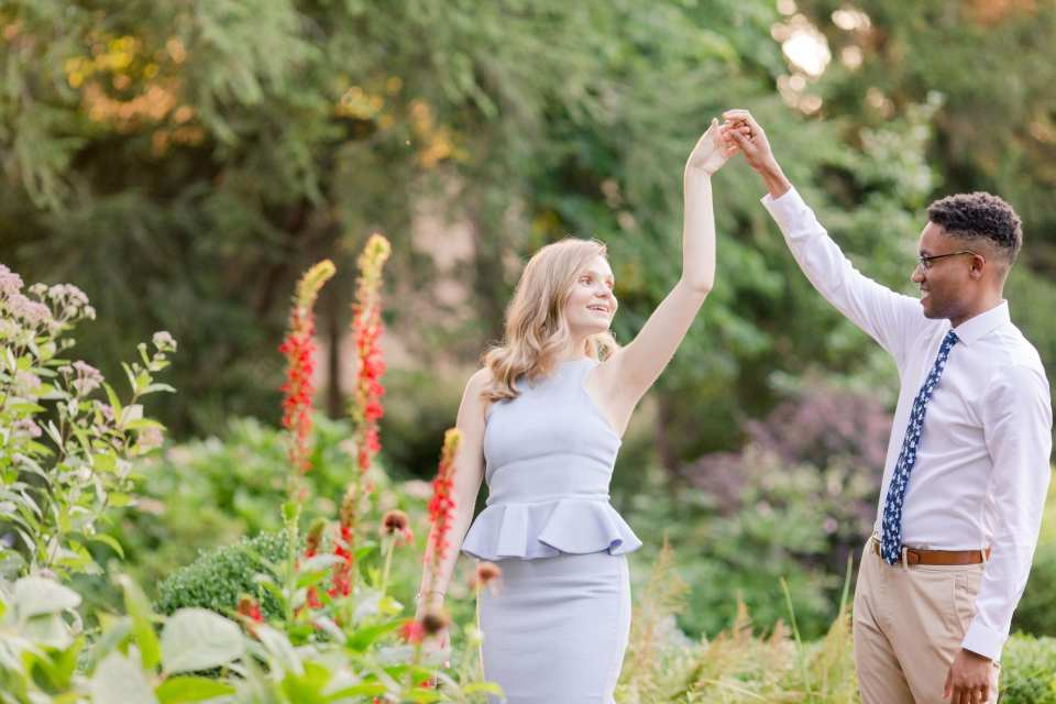 Engaged couple dance and twirl in a garden. She is wearing a pale blue peplum dress by John Paul Ataker from Castle Couture. He is wearing a shirt by Calvin Klein, pants by Old Navy, tie from Bar III. Jaye Kogut Photography, New Jersey engagement photographer