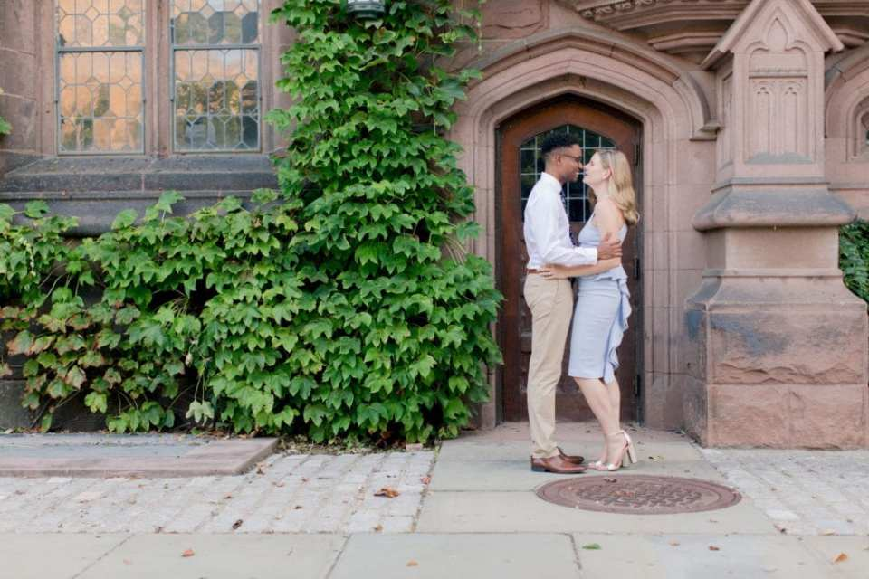 Engaged couple nose to nose in a light embrace on the campus of Princeton University. She is wearing a pale blue peplum dress by John Paul Ataker from Castle Couture. He is wearing a shirt by Calvin Klein, pants by Old Navy, tie from Bar III