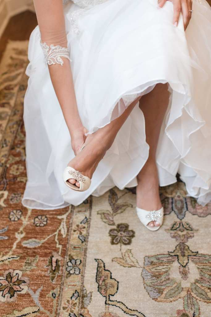 The bride putting on her Badgley Mischka shoes