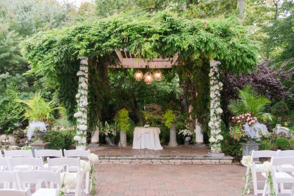 The chuppah decorated with an abundance of greenery, with two columns of white florals by Paradise Flower Shoppe at Nanina's In The Park