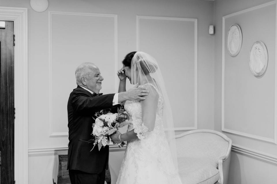 Black and white candid photo of the bride crying during her first look with her father, whom is going in to embrace her