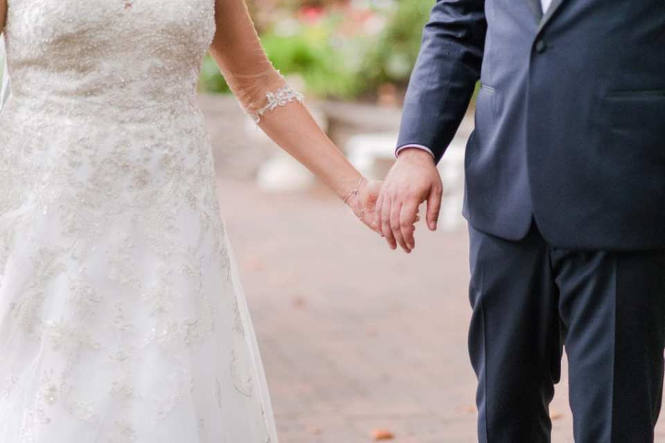 Close up of the bride and groom holding hands, focus on their hands