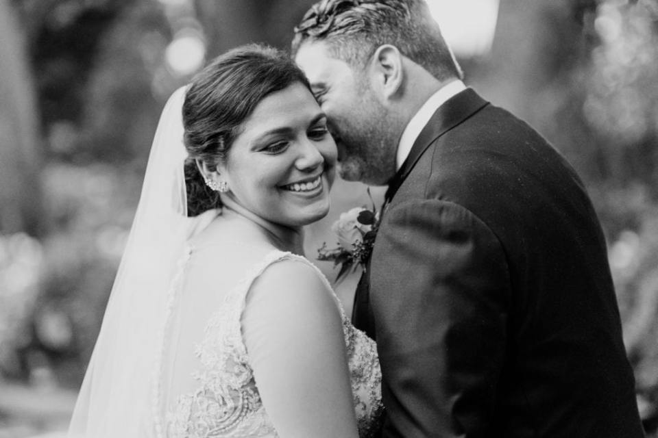 Black and white candid photo of the bride smiling back at the camera as her groom whispers something in her ear