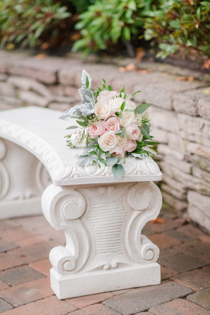 The bridal bouquet of cream and light pink roses by Paradise Flower Shoppe on a white stone bench
