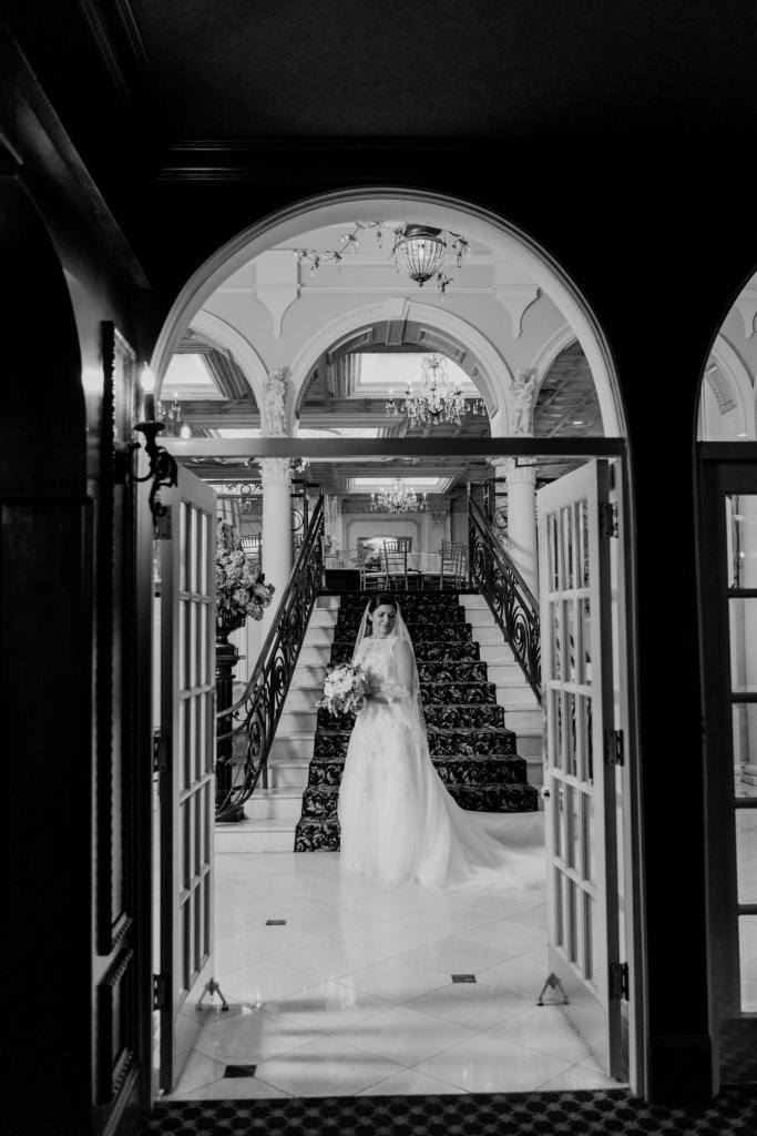 Black and white bridal portrait from a distance through glass doors, in front of the staircase at Nanina's in the Park