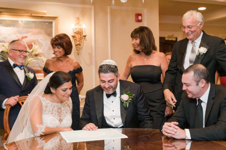 The bride and groom looking over their ketubah with their families looking on with pride