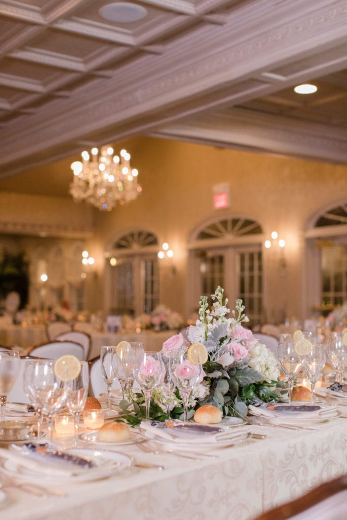 Wedding details: rectangle table in the ballroom at Nanina's in the Park with ivory patterned table cloth and low centerpiece of white and blush pink