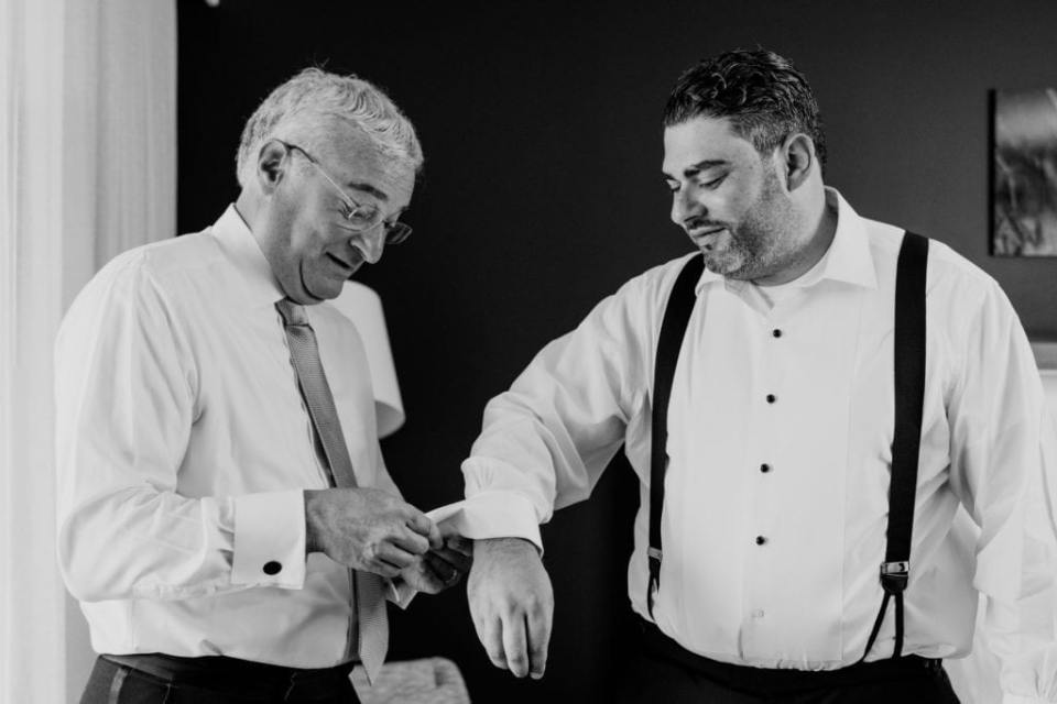 Black and white image of the groom getting assistance from his father with his cufflinks