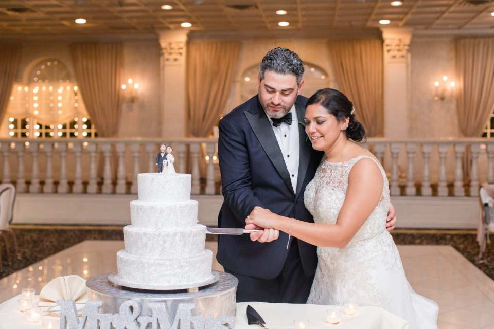 The bride and groom cutting their four tier white wedding cake with silver glitter by Conca D'Oro