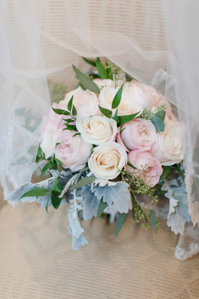 The bridal bouquet of cream and light pink roses by Paradise Flower Shoppe displayed under her veil