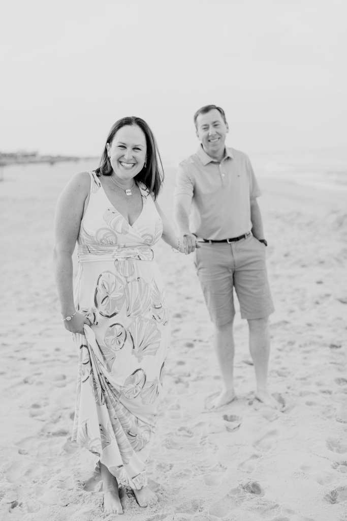 Black and white photo of the engaged couple holding hands and smilingon the beach in Spring Lake
