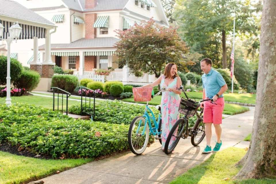 Engaged couple walks alongside antique bikes amongst the homes in Spring Lake, New Jersey. She is wearing a maxi dress by Lilly Pulitzer, he is wearing a blue shirt and coral shorts by Vineyard Vines. By NJ engagement photographer Jaye Kogut Photography