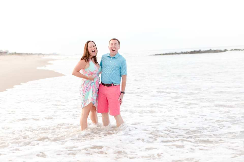 Couple laughing in the surf at Spring Lake Beach. She is wearing Lily Pulitzer, he is wearing Vineyard Vines
