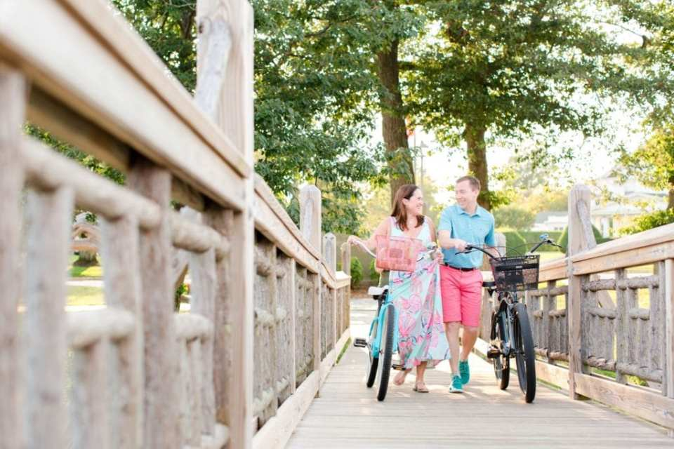 Distance photo of the bride and groom to be laughing while walking alongside antique bikes on a wooden bridge in Divine Park, Spring Lake, New Jersey by NJ wedding photographer Jaye Kogut Photography