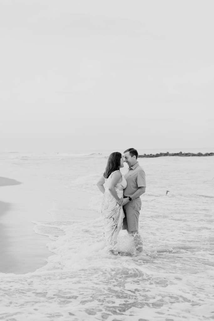Black and white photo of bride and groom standing in the surf on Spring Lake beach, nose to nose.
