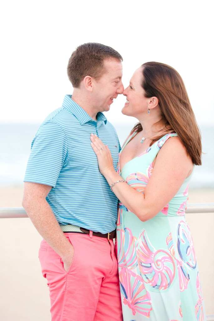 Engaged couple face to face, nose to nose, smiling. Her left hand on his chest, his right hand in his shorts pocket.