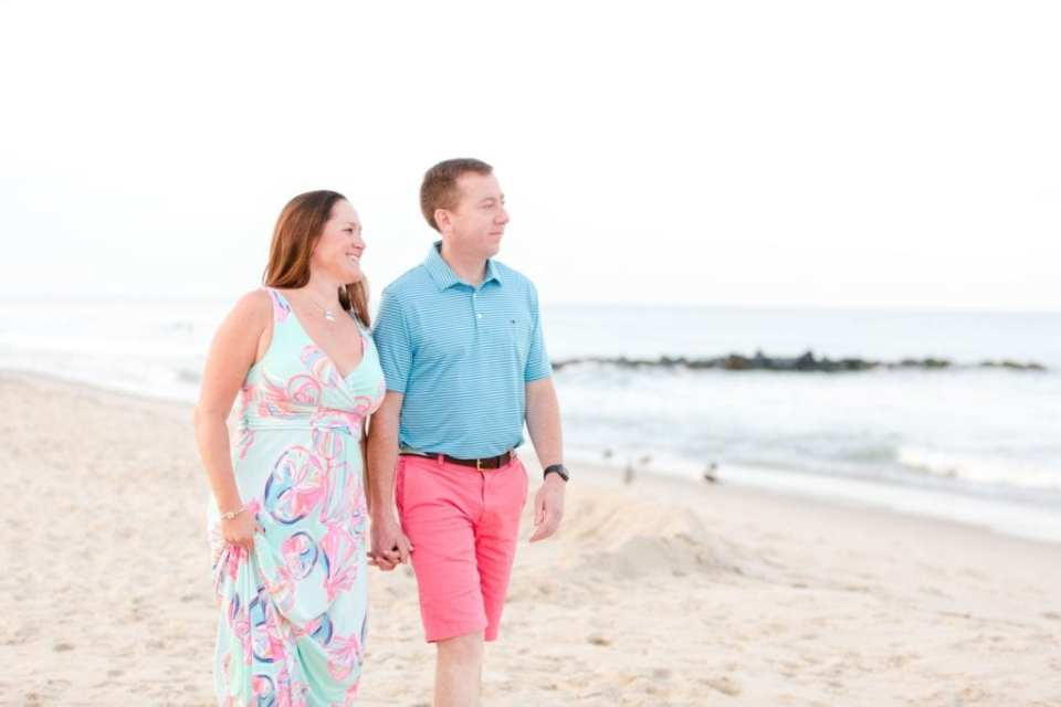 Engaged couple walking hand in hand on the beach, both looking off in the distance towards the ocean. She is wearing a dress by Lily Pulitzer