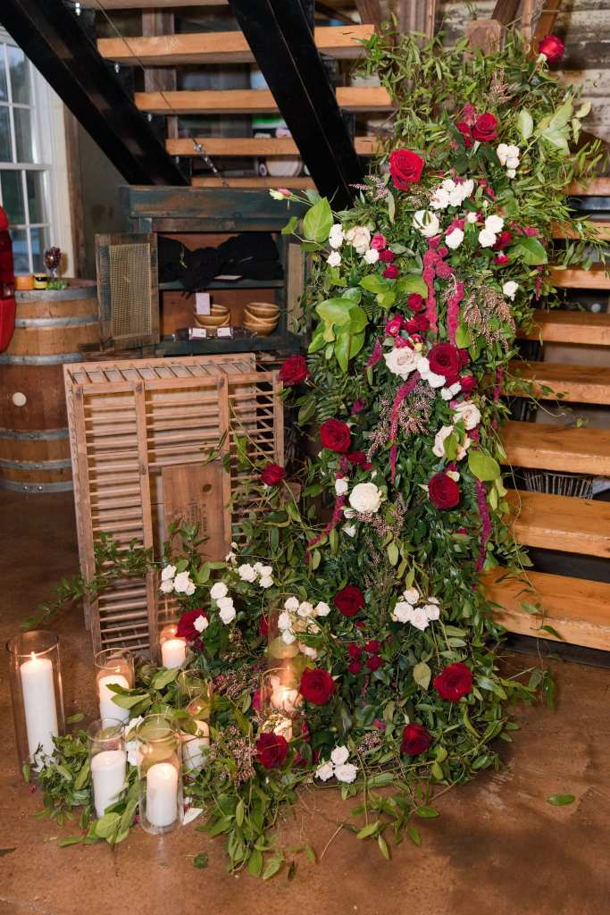 floral decor on the stairs at the Laurita Winery of greens with red and white florals by Ivy on Main
