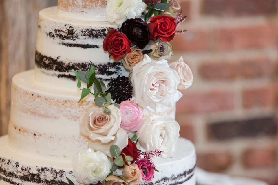 close up photo of the semi-naked cake from Conroy Catering with rose accents in shades of cream, white, pink and red