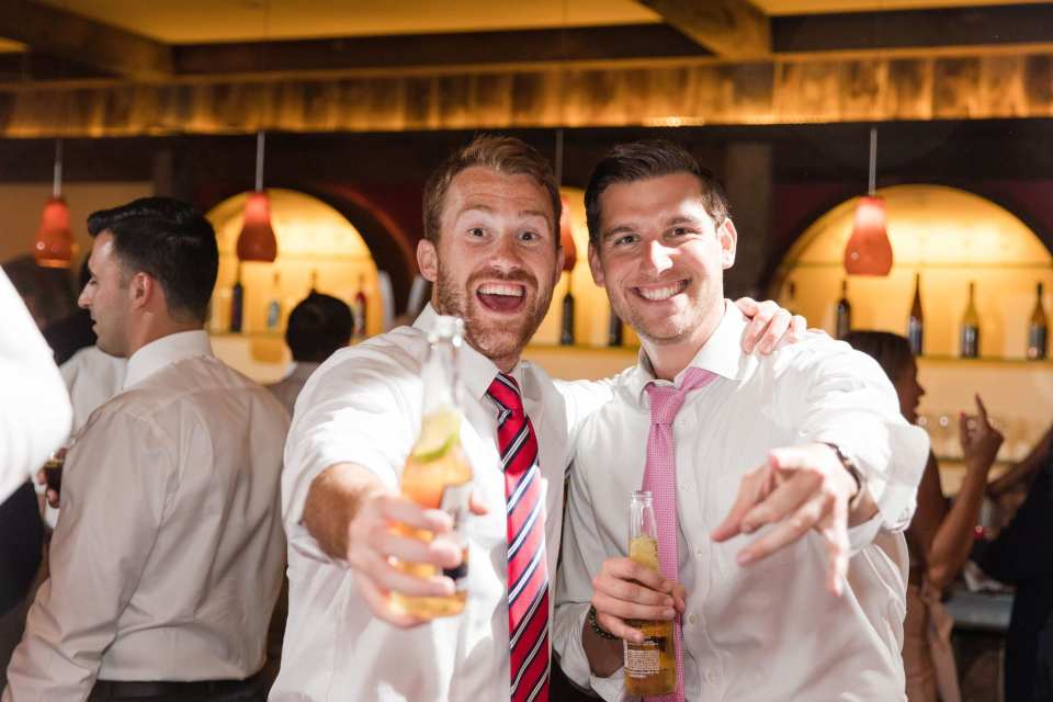 guests smile for the camera while holding beer