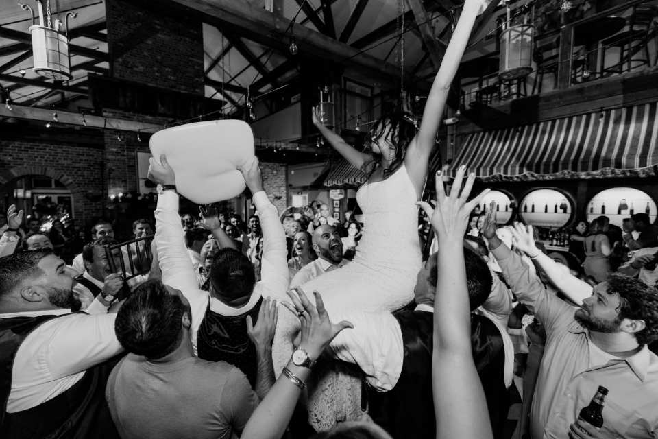 Black and white photo of bride up on chair during the Hora