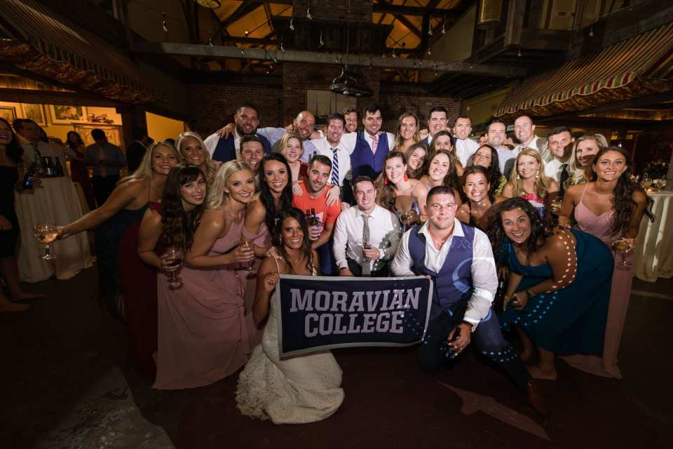 Bride and groom take large group photo with classmates from college while holding signage from their college