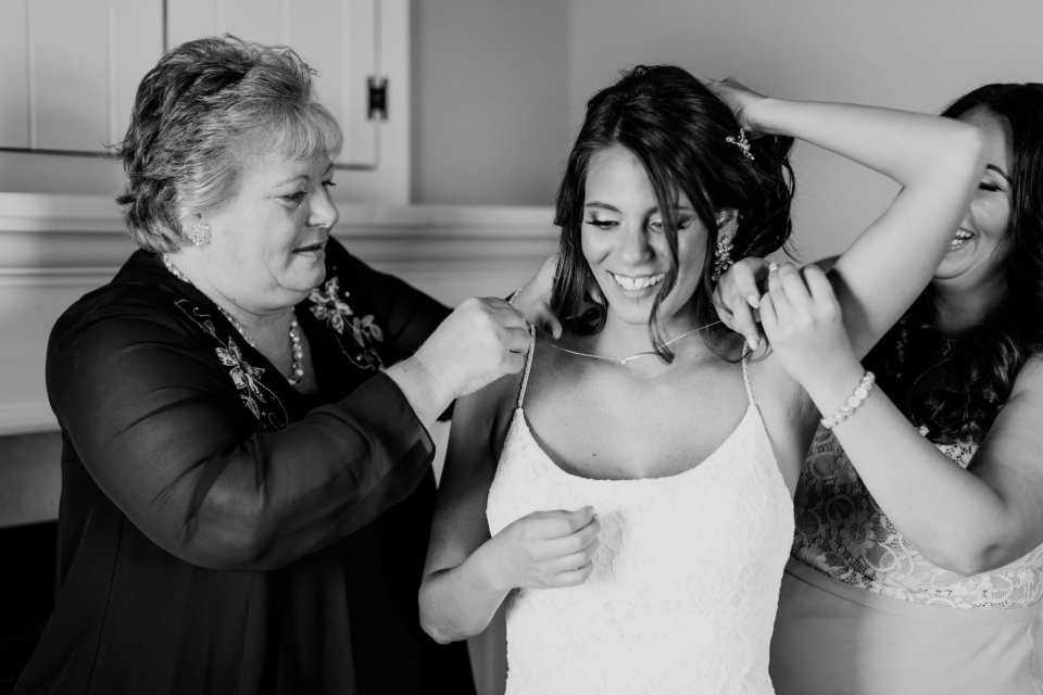 black and white candid photo of the brides mother and sister helping her put on her necklace