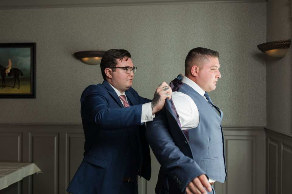 Brother of groom helps the groom into his suit jacket by Generation Tux